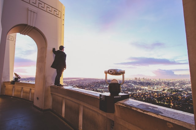 man standing on edge overlooking a city