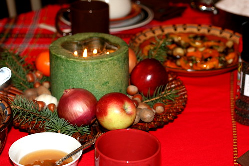 Festive table decorated with candles, fresh fruit, nuts, whole onions and garlic in hope to bring abundance next year