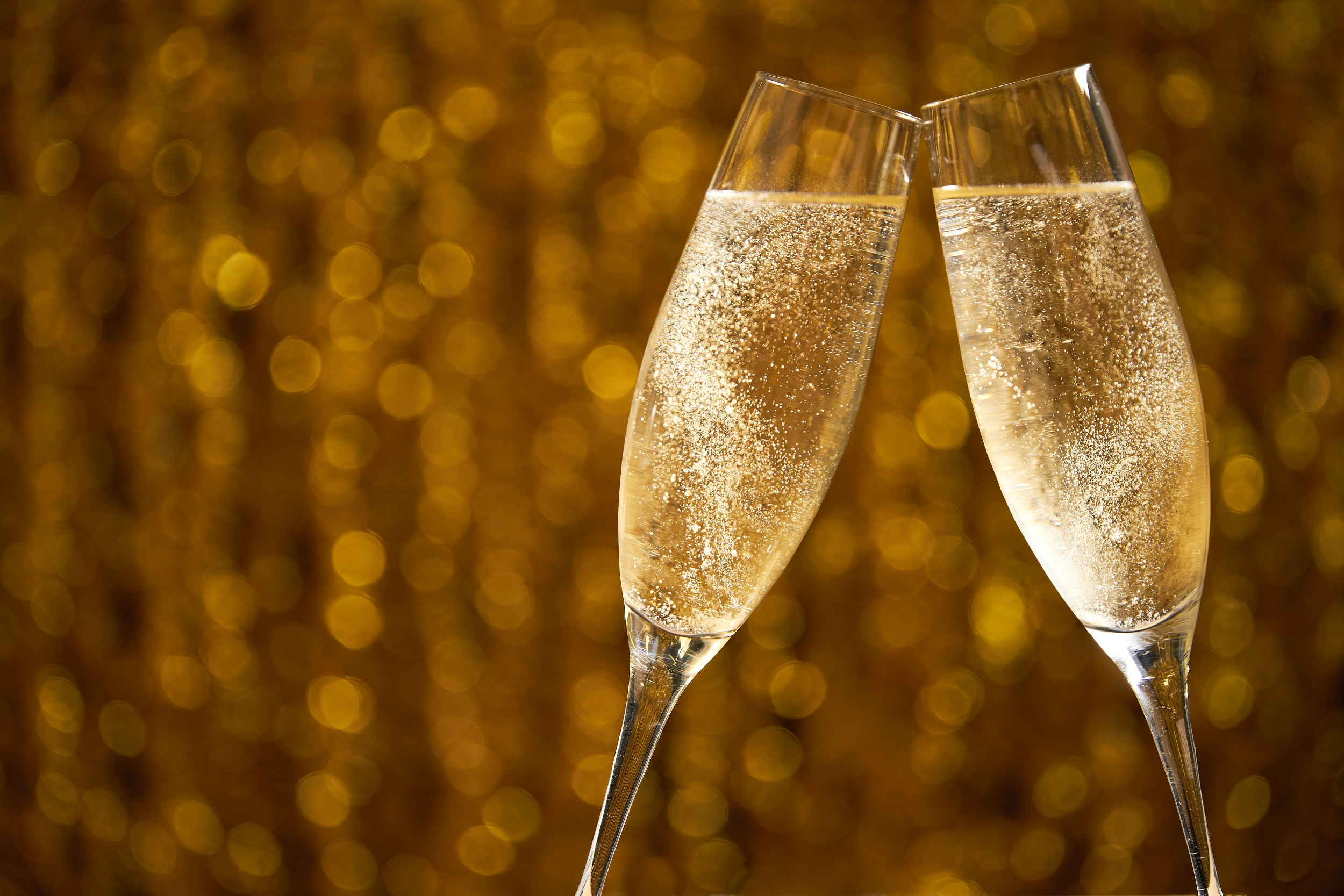 two glasses of champagne on golden stylish background