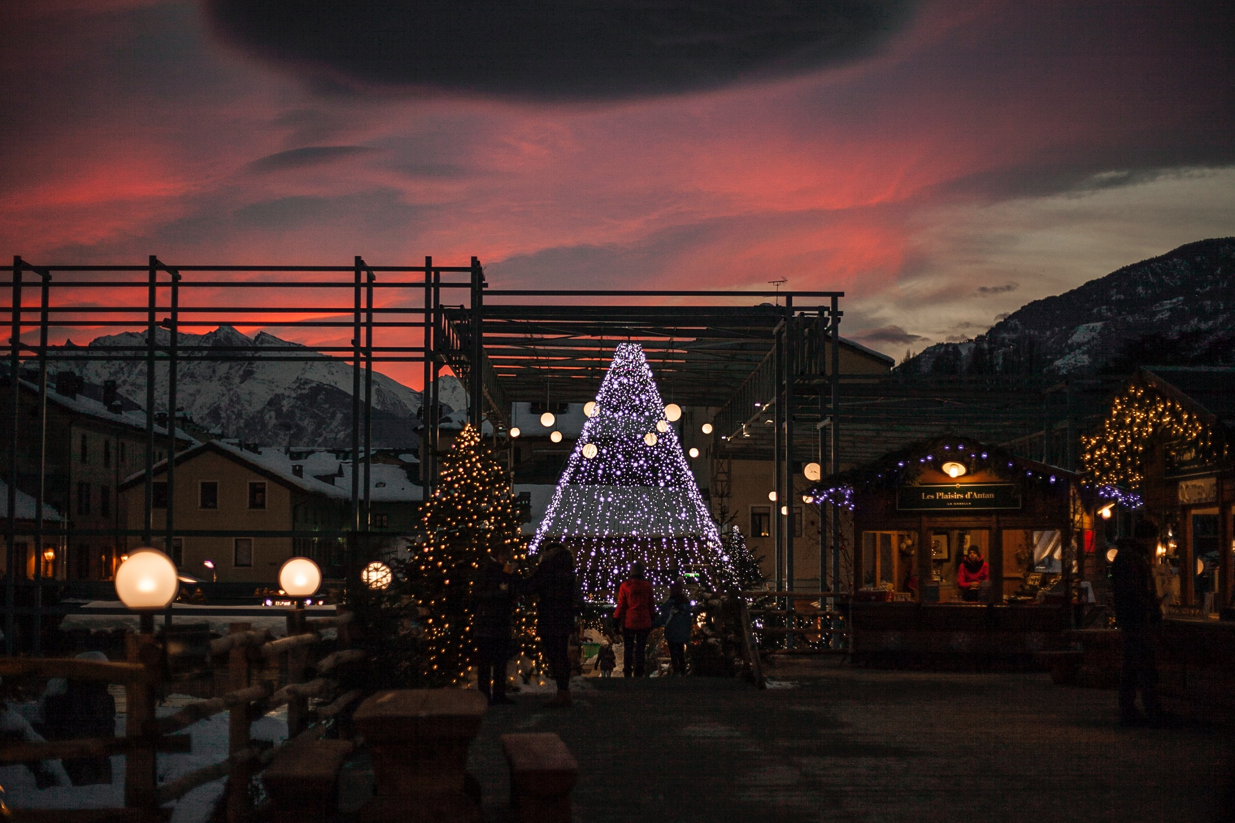 Christmas market with the sun setting and snowy mountains