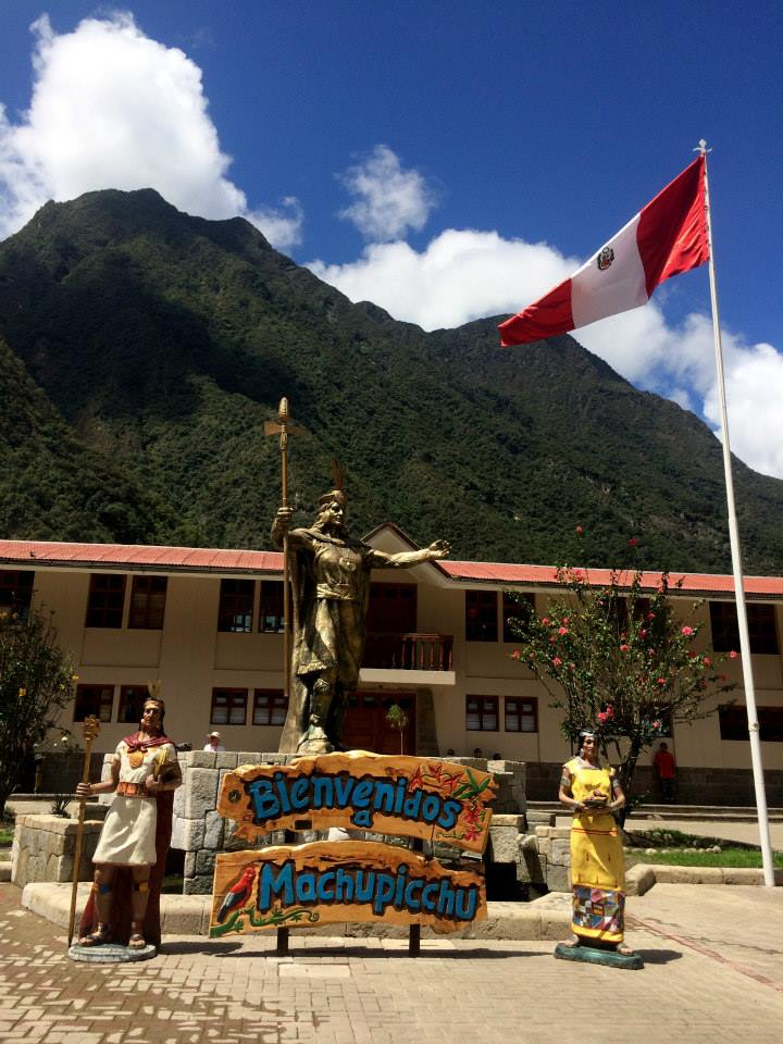 Statue in plaza with sign that reads Bienvenidos a Machupicchu
