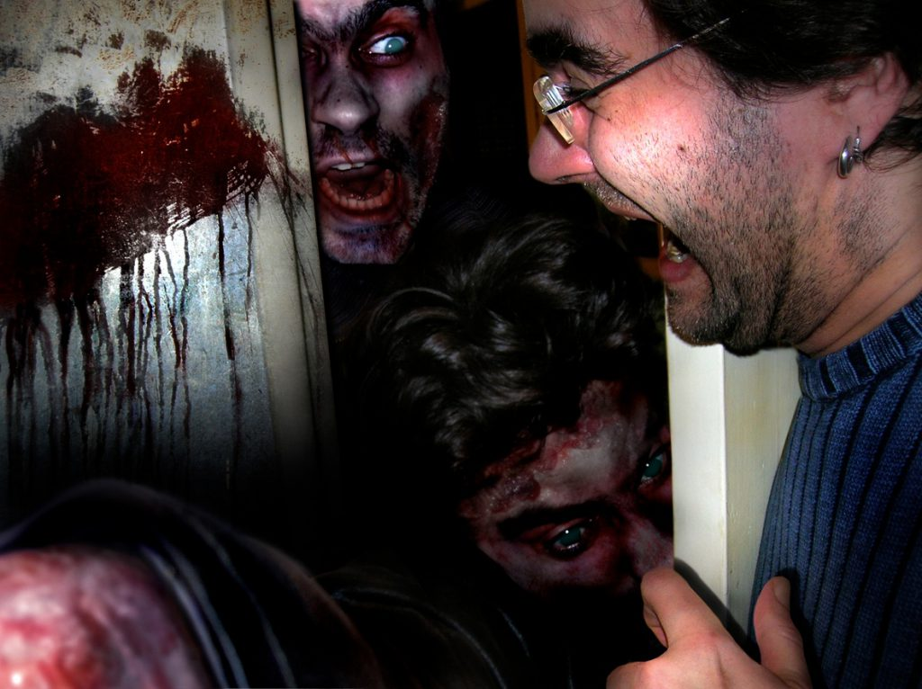 Scared man with zombies trying to break through a door