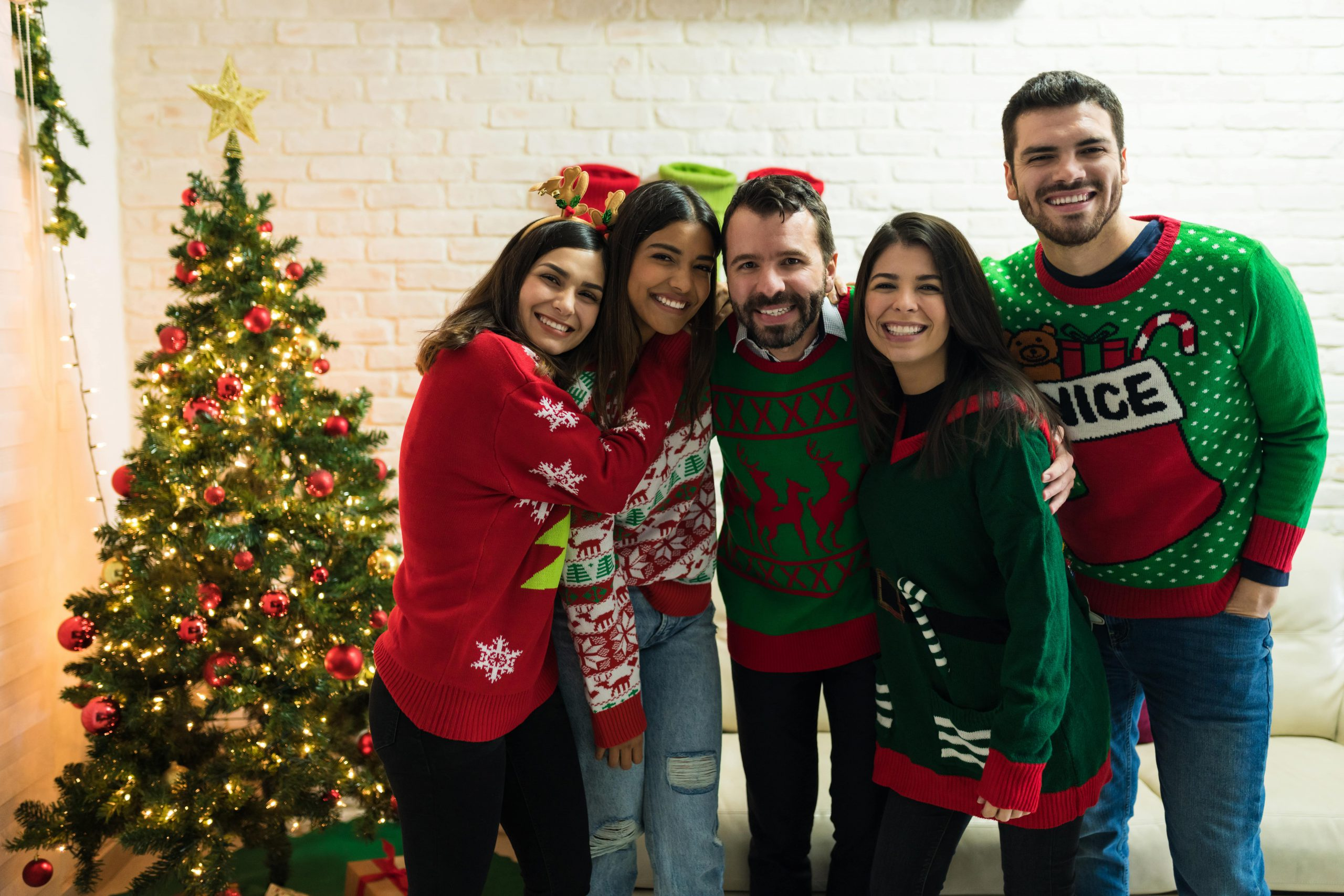 Group of friends wearing ugly Christmas sweaters