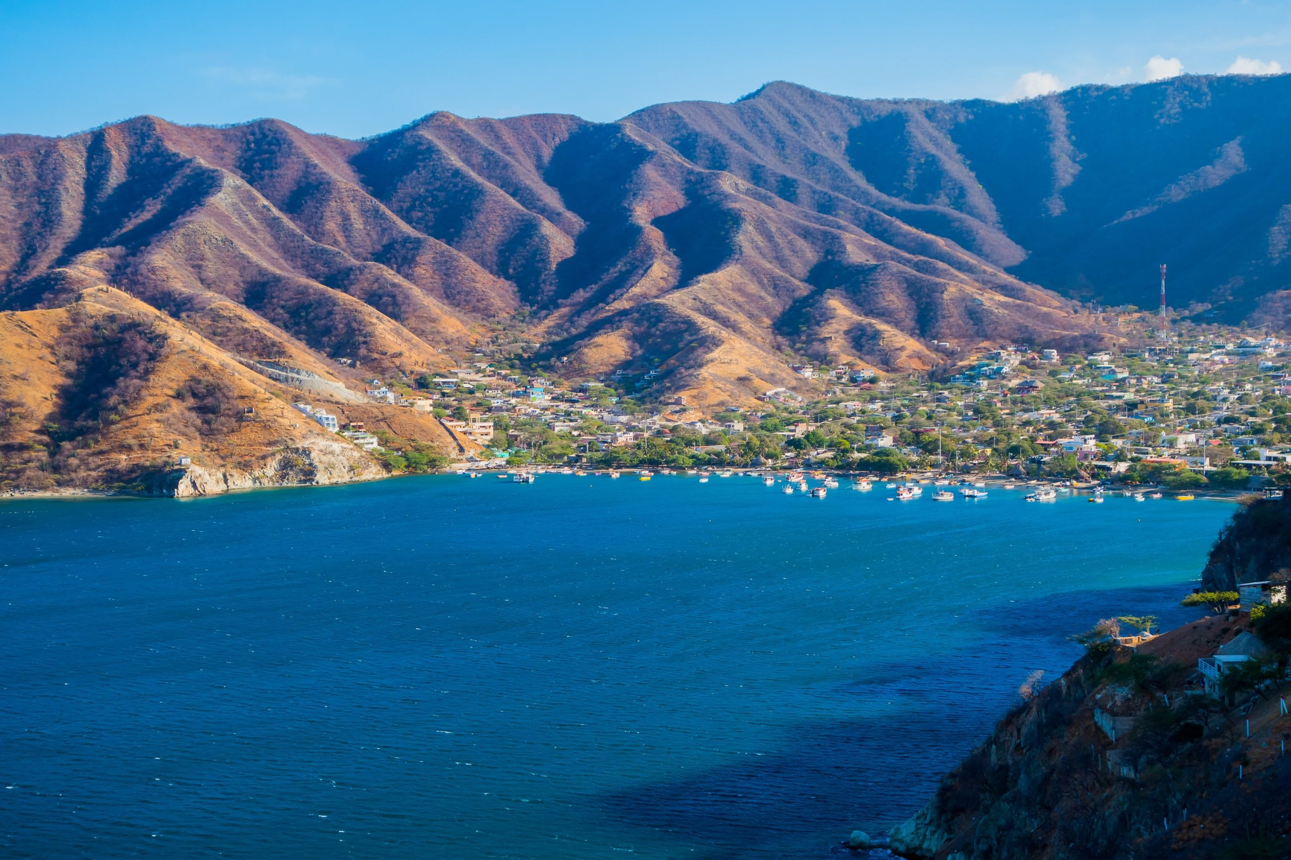 Photo of an ocean coast with a town and mountains