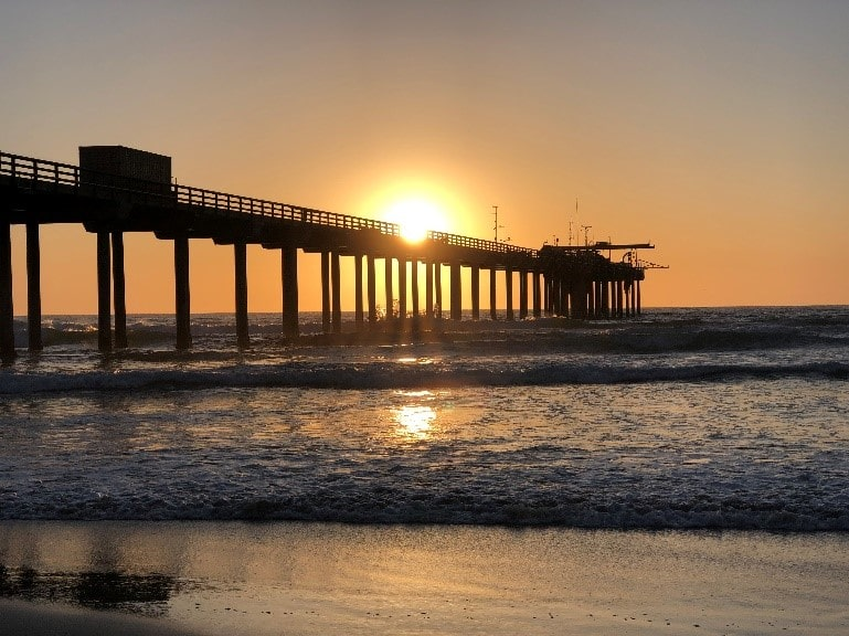 Pier on the beach at sunset