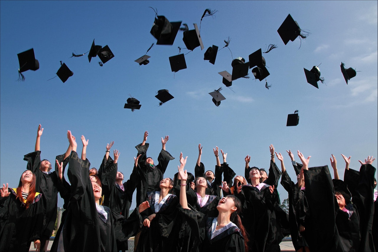 College students graduate and throw their caps into the air