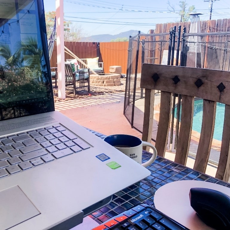 Laptop outside in front of a patio and pool with mountains in the background