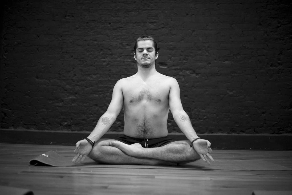 Male sitting cross legged meditating