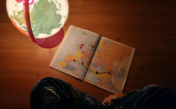 Person sitting on the floor looking at a map and a globe