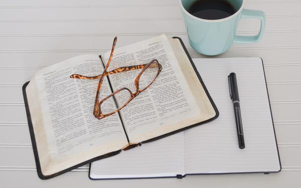 Notebook, book, and glasses on a table next to a cup of coffee