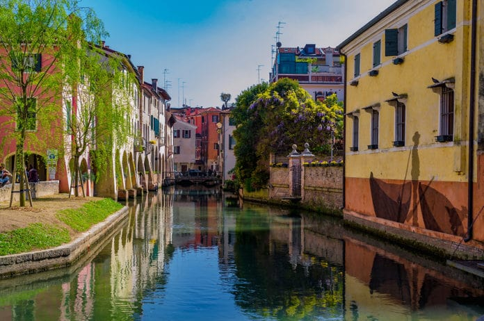 Beautiful and colorful canal through buildings in Italy