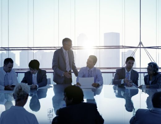 Business people sitting around a conference table with a skyline at sunset in the background