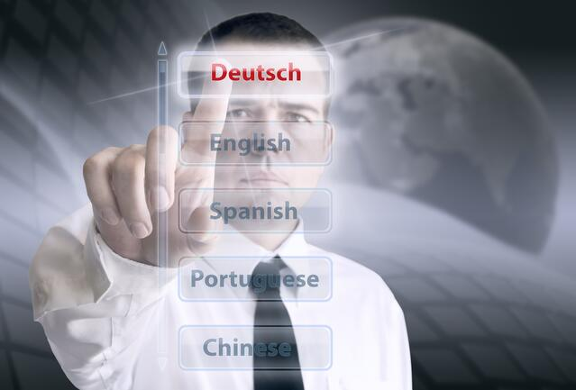 "Buttons with various language names with a man pressing ""Deutsch"""